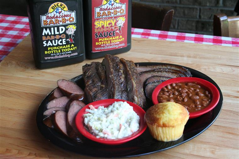 cornbread, coleslaw, baked beans, barbeque ribs on a plate with mild and spicy sauce in containers