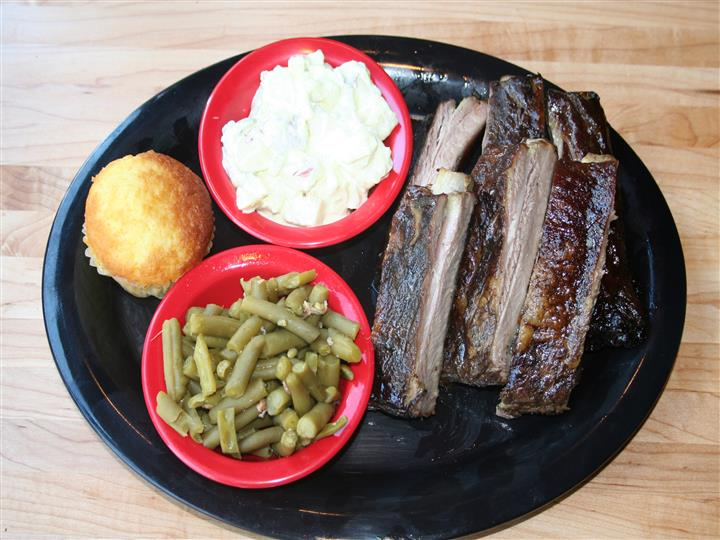 ribs with sides of green beans, potato salad and corn bread