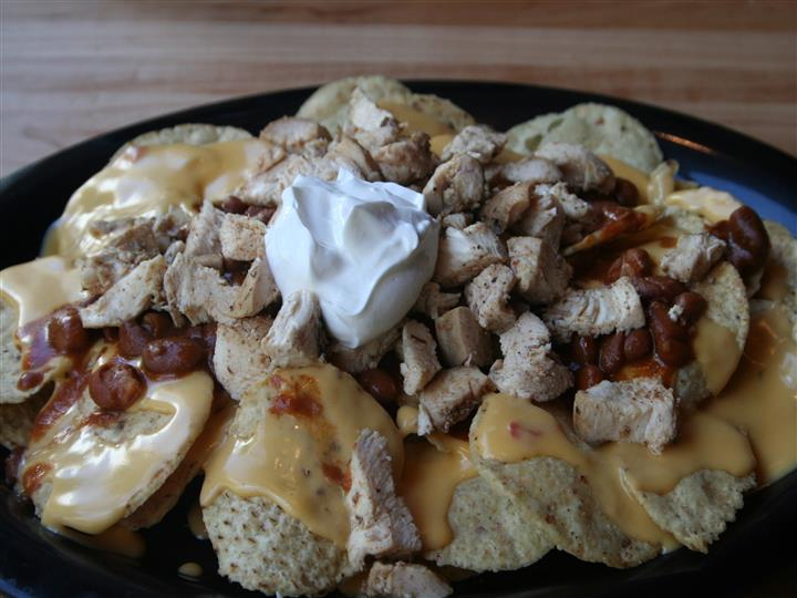 nachos with chicken, baked beans, nacho cheese and sour cream