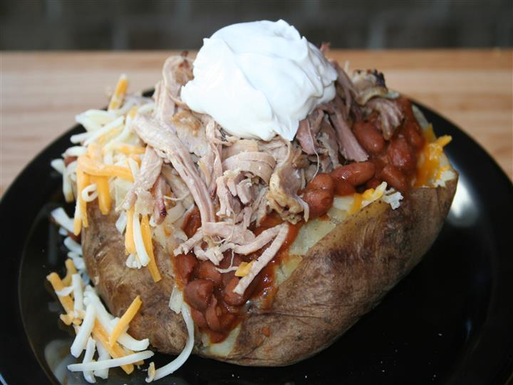 baked potato with baked beans, shredded pork, sour cream and shredded cheese