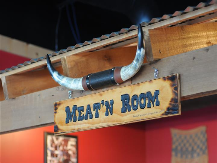 "a sign that reads, ""Meat'n Room"", with decorative bull horns"