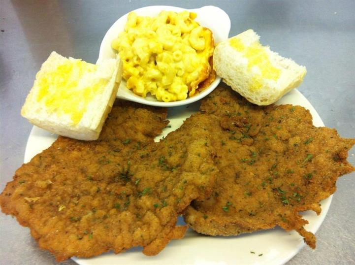 two pieces of country fried steak with two pieces of bread and mac and cheese