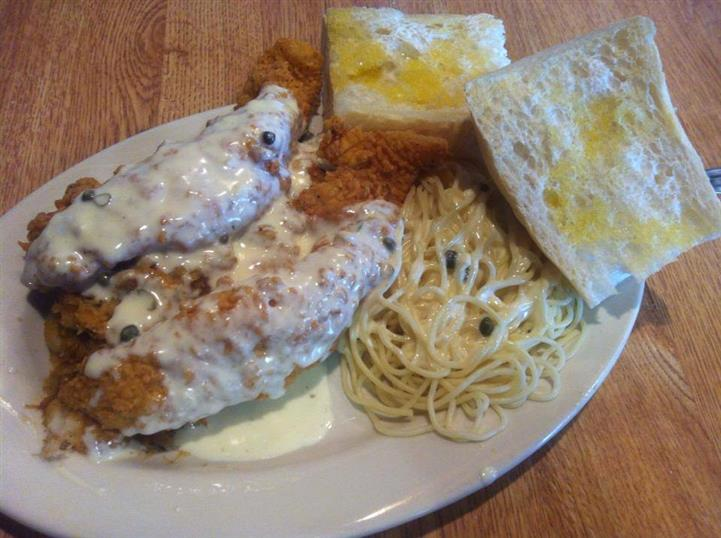 fried fish smothered in gravy with noodles and bread