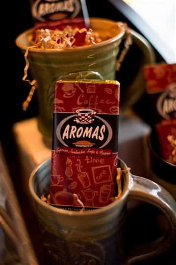 coffee cup with chocolate bar inside with the aromas logo