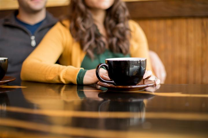 coffee cup on table with a male and female sitting in the background