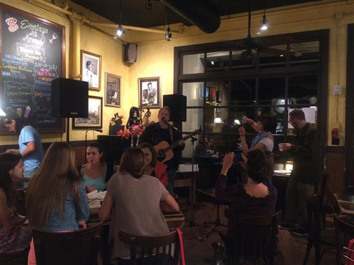 band playing inside aromas with singer playing guitar