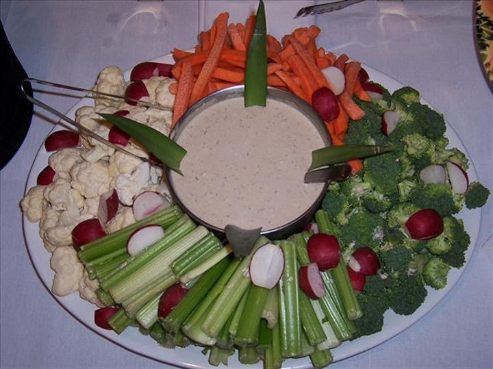 various vegetables on a plate with dipping sauce in the middle