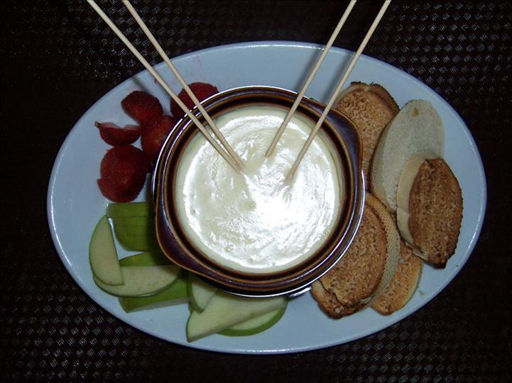 carrots and crackers on a plate with dipping sauce in the middle