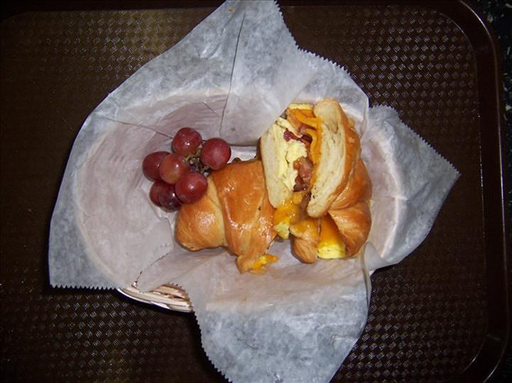 croissant sandwich cut in half with a side of red grapes