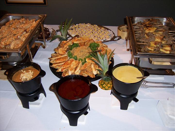 buffet table with trays and a variety of food items with sauce