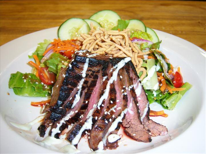 house salad with flank steak drizzled with dressing on a plate