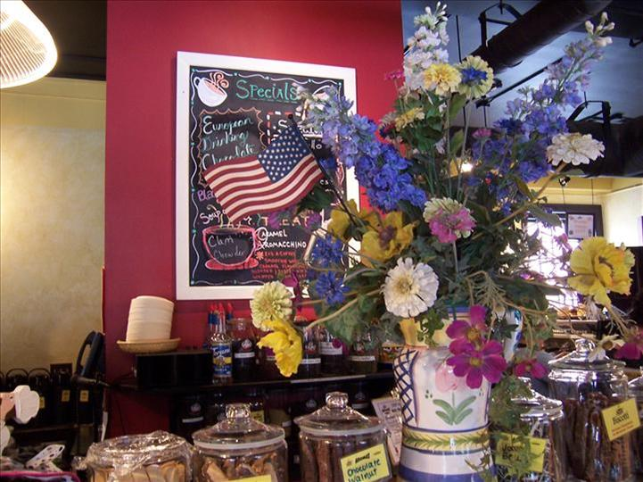 view of the counter with flowers and a menu with american flag on chalkboard