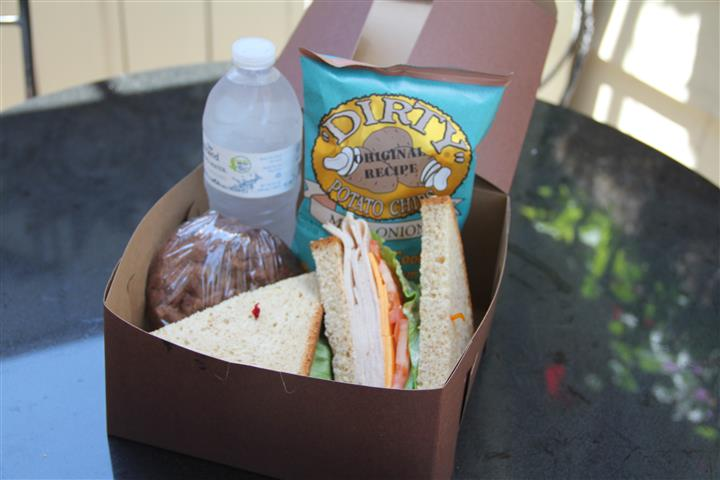 sandwiches with a bag of chips, grapes and a bottle of water