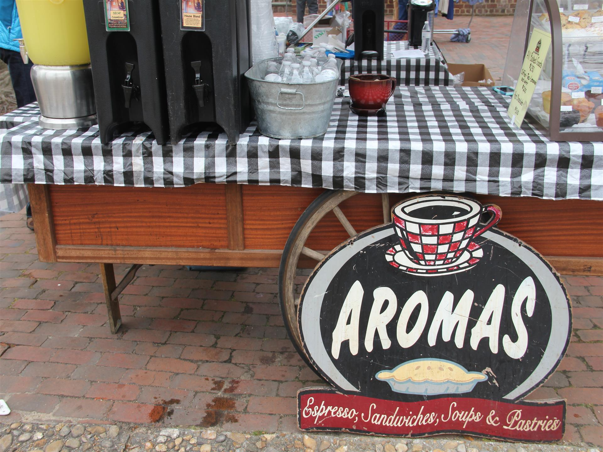 Aromas - Espresso, sandwiches, soups and pastries sign in front of outdoor display.