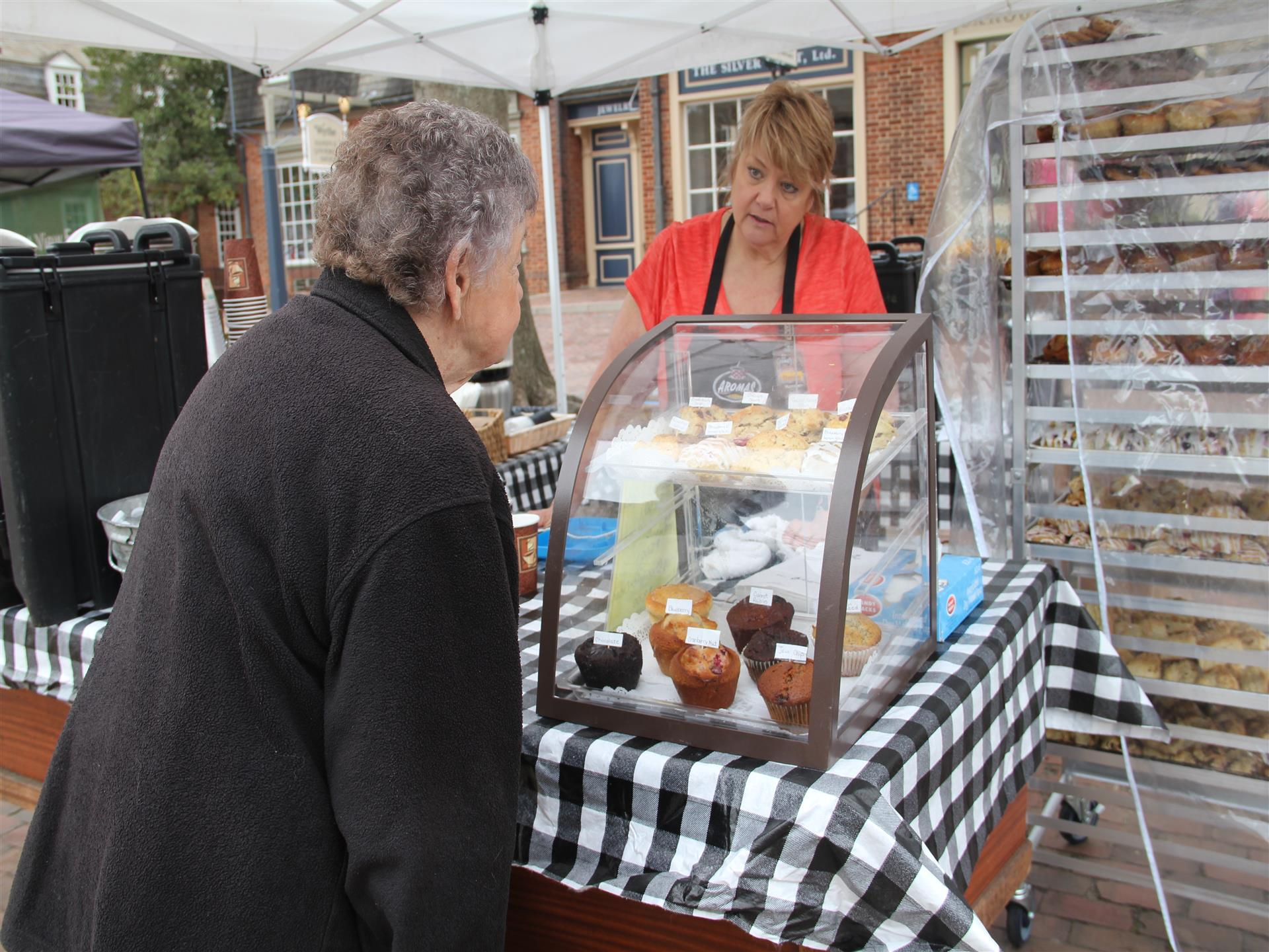 Woman looking at muffins at Aroma's outdoor stand at farmer's market.