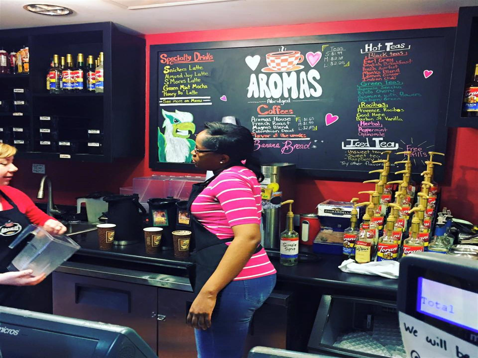 workers behind counter with menu on black chalkboard in background