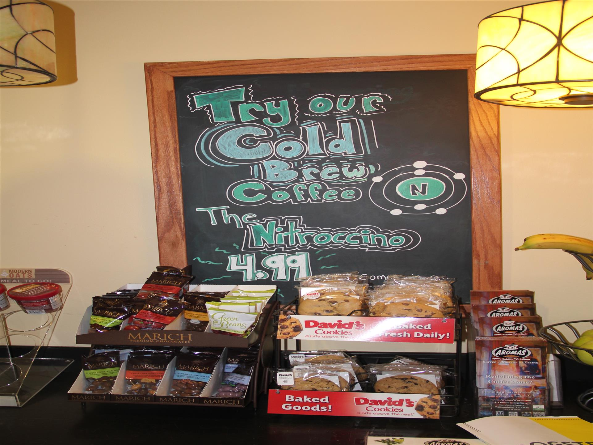 close-up view of counter with various menu items available to grab-and-go with menu on black chalkboard above table
