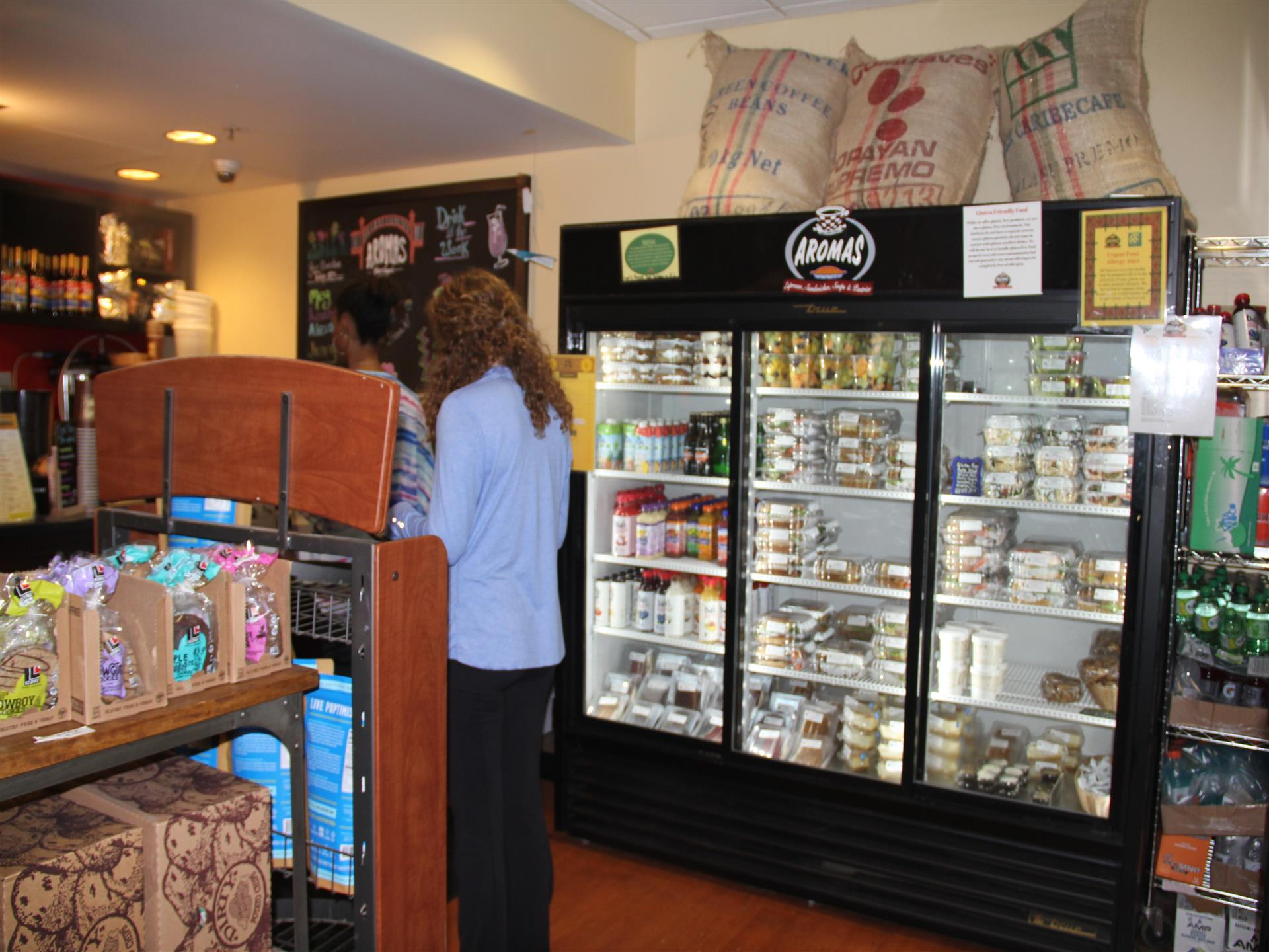 customers standing in line to place their order with various refrigerated items in background