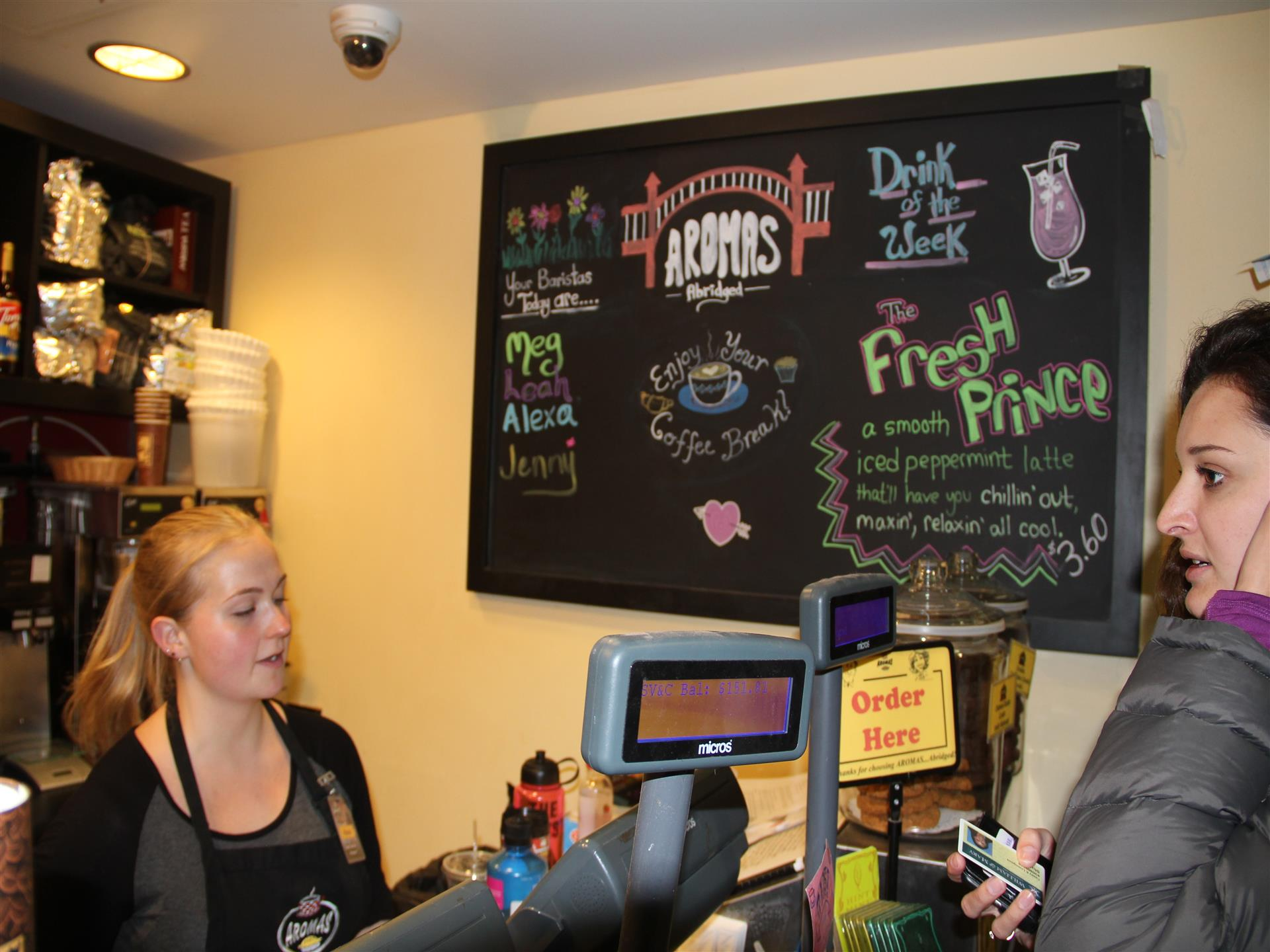 person ordering coffee with worker behind counter taking order with menu on black chalkboard