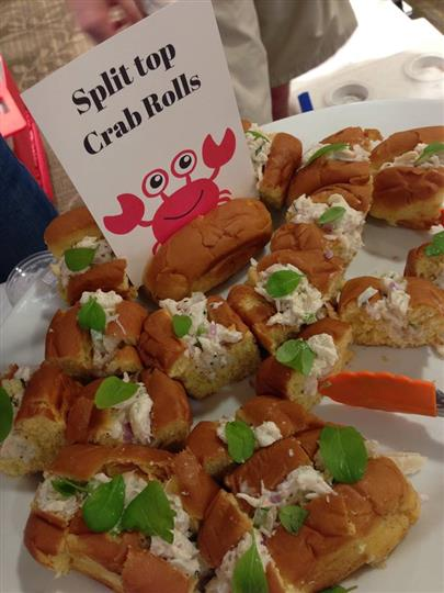 tray of crab rolls with a sign that reads split top crab rolls