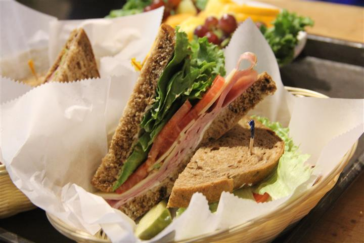 turkey sandwich topped with cheese, lettuce and tomato cut in half