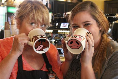 two workers drinking from coffee mugs