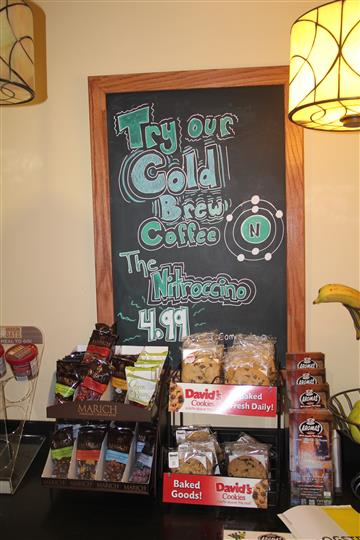 coffee in bags ready to buy on a counter with message on chalkboard