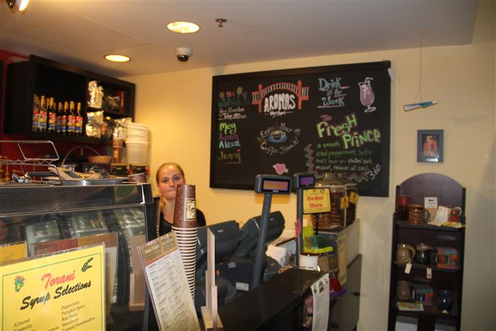 worker behind counter with menu on chalkboard