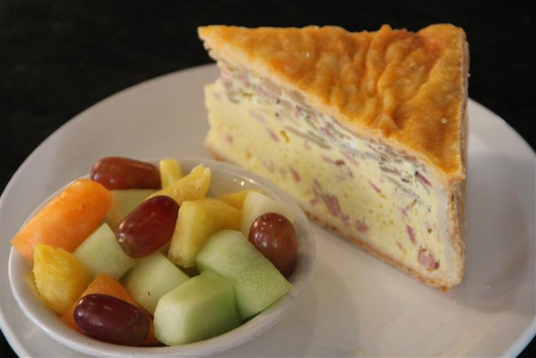 Quiche slice and small fruit salad on white dish.