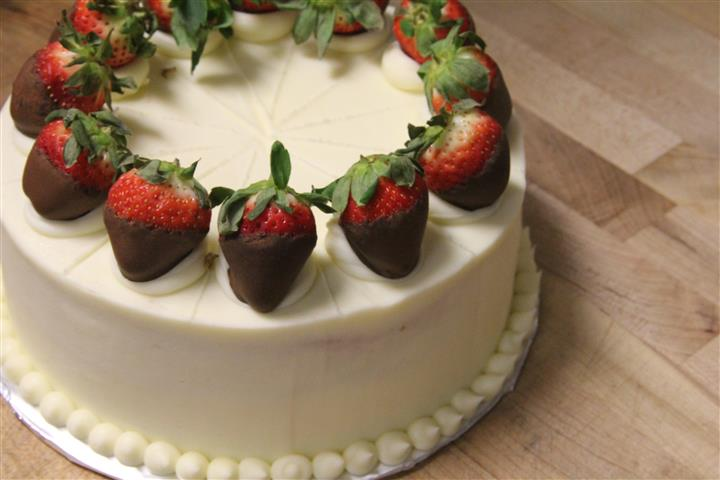 Champagne infused cake with champagne flavored buttercream. Chocolate dipped strawberry garnish.