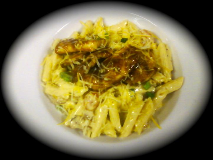 penne pasta topped with chicken and melted cheese
