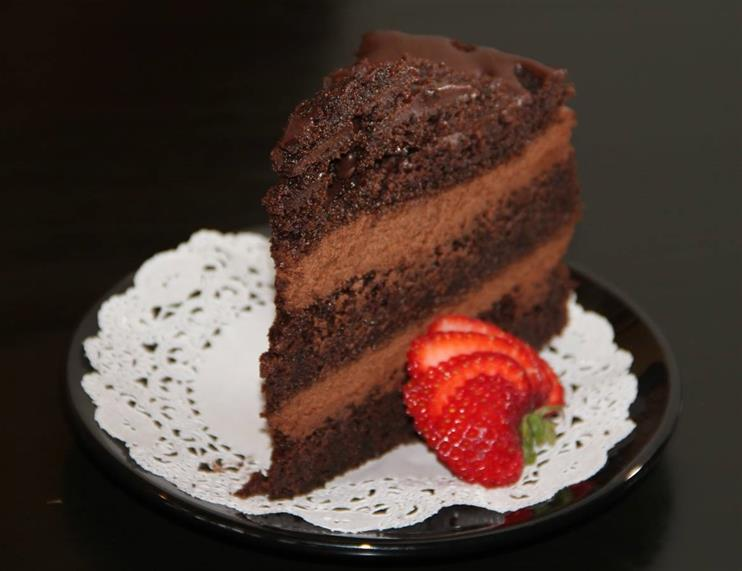 Multi-layered chocolate cake with cut strawberry on doile on black dish.