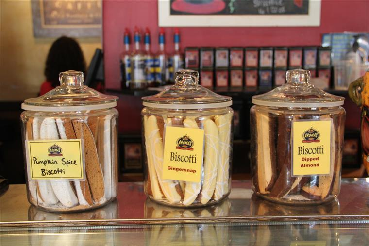 Biscotti in large jars on countertop. Pumpkin spice biscotti, gingersnap biscotti, dipped almond.