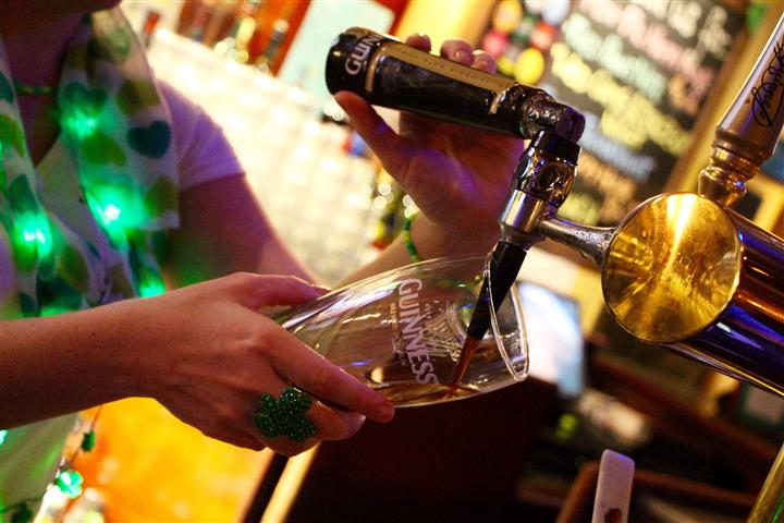 Bartender filling Guinness glass with beer for a tap