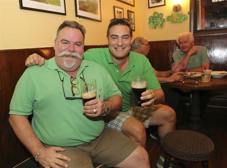2 Men with beers in their hand smiling