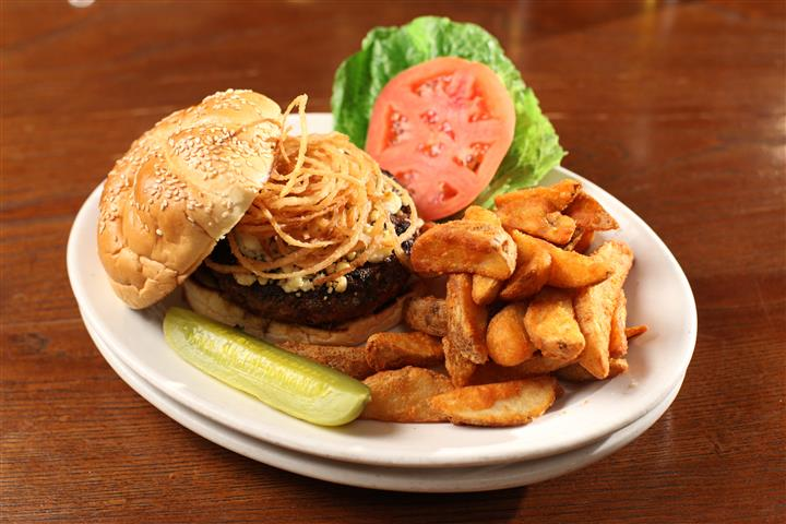 Cheese burger with a side french fries alongside lettuce, tomato, and pickle slice