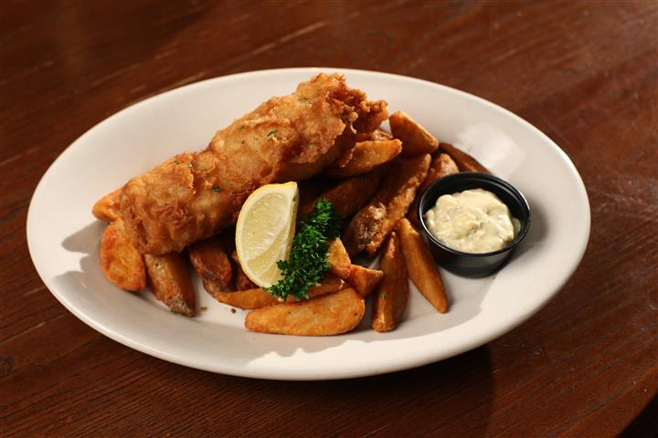 Fish and french fries with a lemon garnish