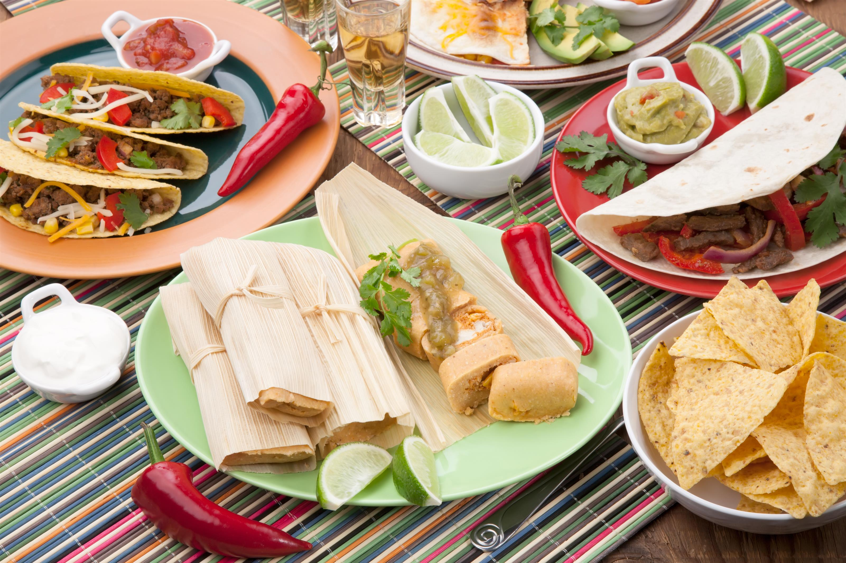 Authentic Mexican spread featuring temales, tacos, tortilla chips, surrounded by chili peppers and limes all on colorful dishes