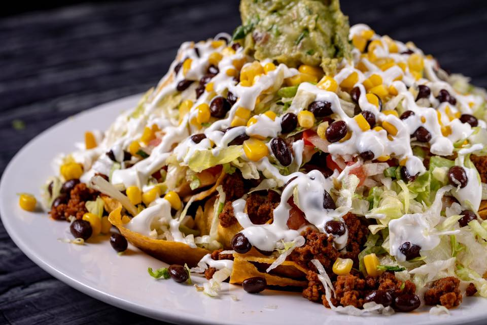 Supreme Nachos: Fresh nacho chips with ground beef, black beans, corn, queso dip, lettuce, pico, sour cream and guacamole.