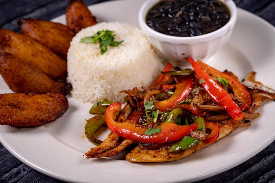 grilled chicken topped with bell peppers with rice, beans, and fried plantains on the side.