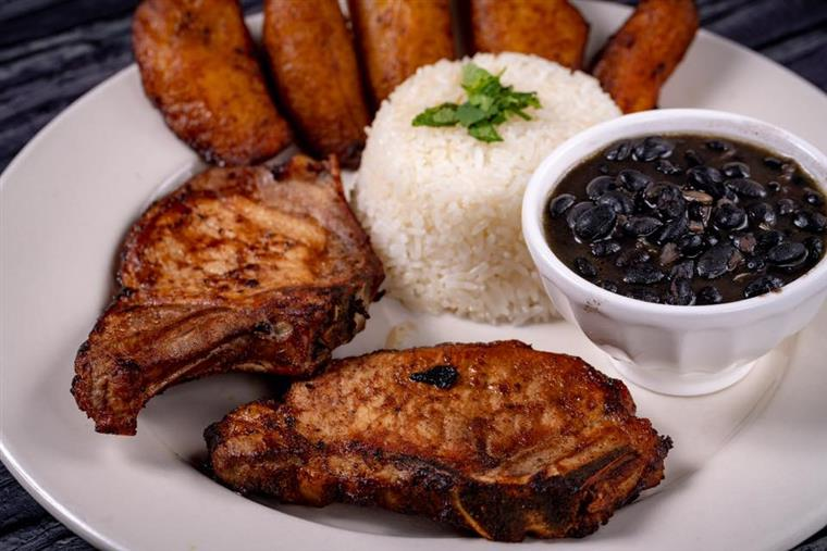Fried pork chop with rice, beans, and fried plantains