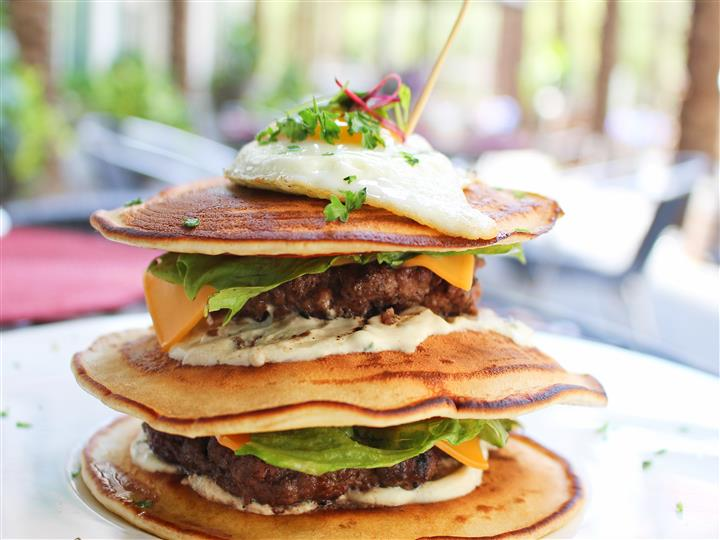 Stack of pancakes with burger patties and sauce in between topped with a fried rgg and sprinkled with fresh oregano