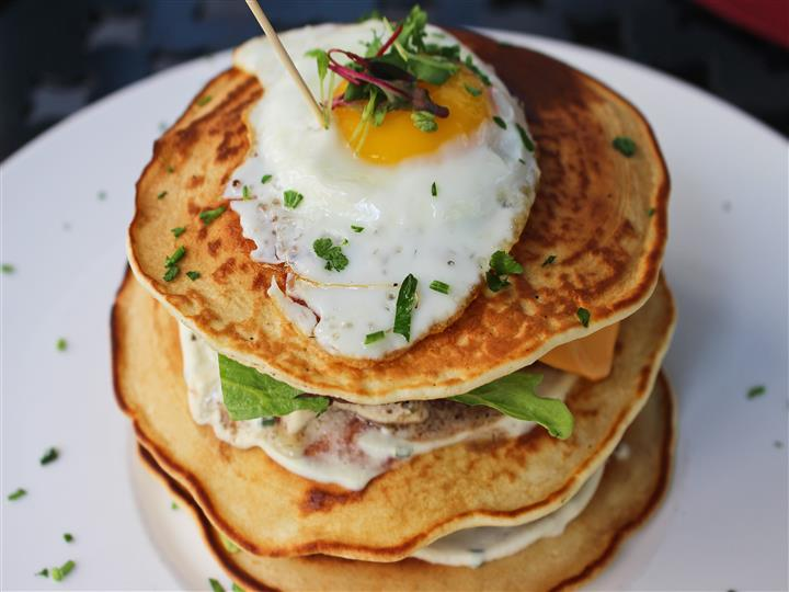 Stack of pancakes with a fried egg on top sprinkled with fresh oregano
