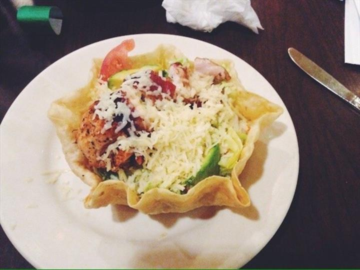 chicken with cheese, tomatoes and avocadoes in a tortilla bowl