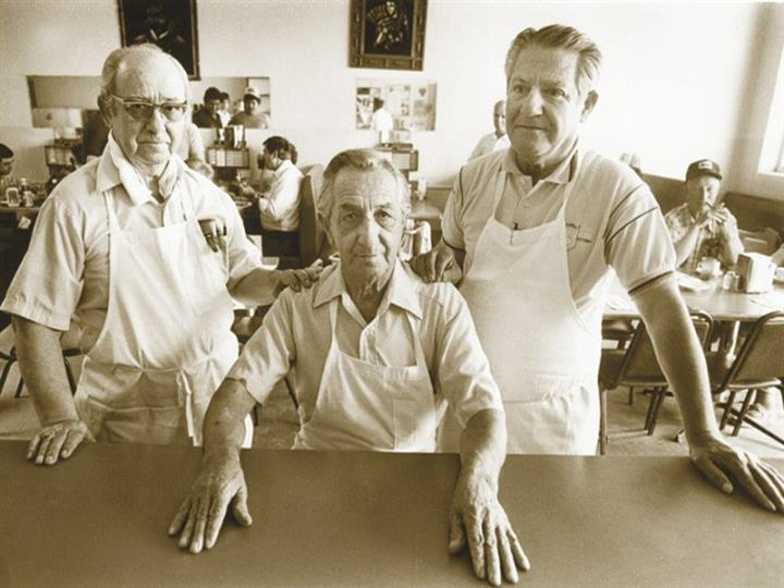 a vintage picture of three men in aprons looking proud