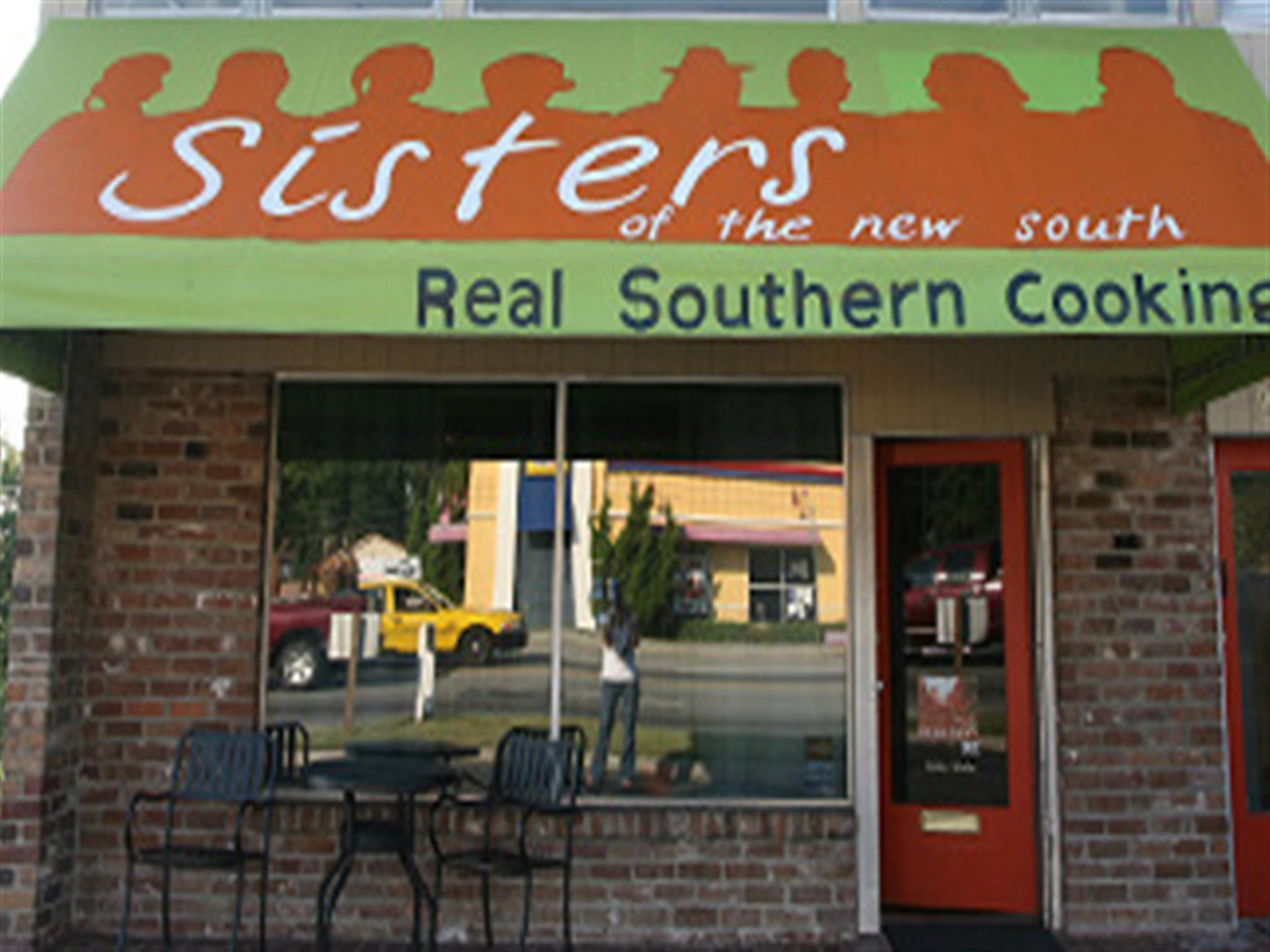 Sisters of the new south. Real southern cooking on green and orange awning above storefront entrance.
