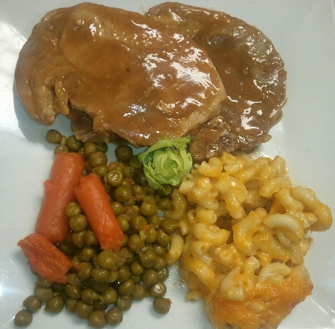 pork chop with gravy, peas, mac and cheese, and carrots