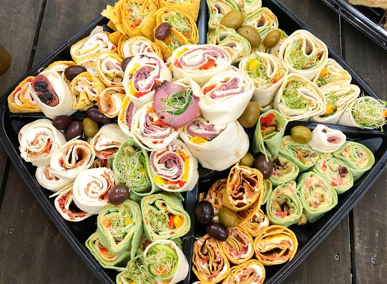 variety of pinwheel wraps on a catering tray