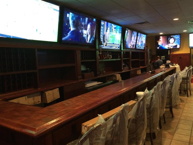 Bar area with TVs behind bar