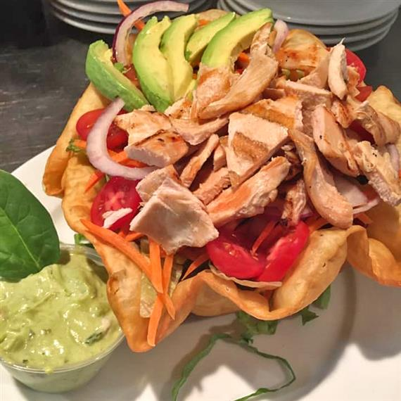 A taco shell slaad topped with avocado, red onion, grilled chicken, tomato and a side of guacamole